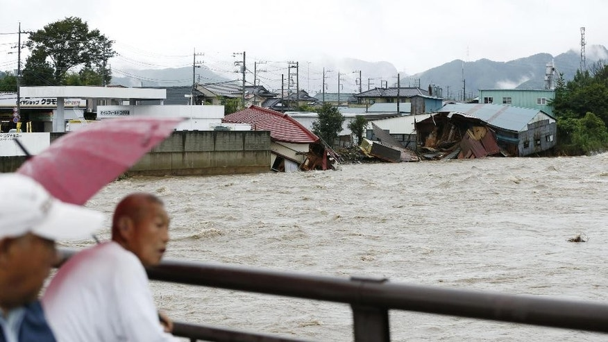 People check the situation as the buildings, background, were damaged by flooding in Kanuma, Tochigi prefecture, north of Tokyo Thursday, Sept. 10, 2015. Heavy rains batter Japan for the second day, causing flooding and landslides in eastern Japan. (Kyodo News via AP) JAPAN OUT, MANDATORY CREDIT