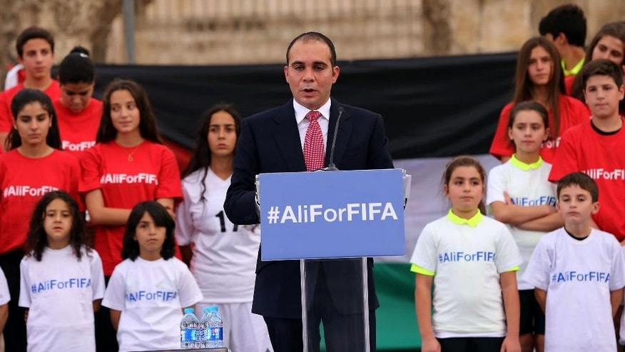 "Jordan's Prince Ali bin al-Hussein, flanked by school-age soccer players in uniforms, speaks before about 300 guests during an event at a Roman amphitheater in Amman, Jordan, Wednesday, Sept. 9, 2015. The prince is running for FIFA president, saying Wednesday he will fight ""deep-seated corruption and political deal-making"" and make soccer's scandal-scarred governing body more transparent. (AP Photo/Raad Adayleh)"