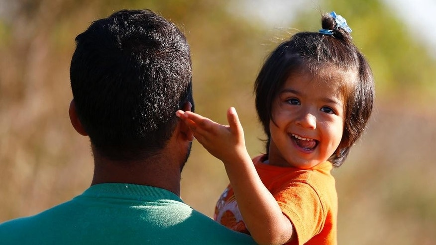 An afghan girl smiles as she and her father cross the border line between Serbia and Hungary near Roszke, southern Hungary, Wednesday, Sept. 9, 2015. Migrants anxious to pass through Hungary towards central Europe are making their way on foot at Hungary's southern border with Serbia. (AP Photo/Matthias Schrader)