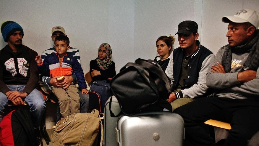 A group of refugees waits after an overnight bus trip from Germany, in Champagne-sur-Seine, south of Paris, France, Wednesday, Sept.9, 2015, the first among around 1,000 that French President Francois Hollande pledged to receive from the neighboring country. (AP Photo/Thibault Camus)