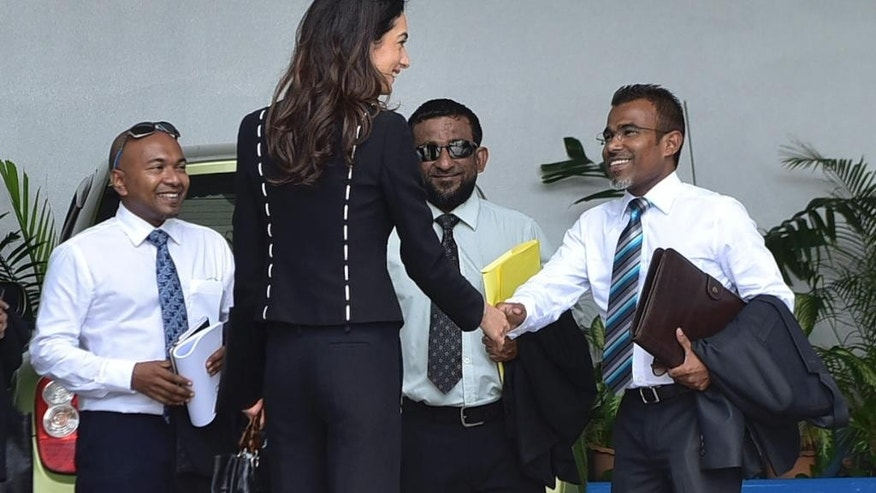 Human rights lawyer Amal Clooney, back to camera, greets ormer president Mohamed Nasheed's lawyers at the High Court in Male, Maldives, Wednesday, Sept. 9, 2015. Amal Clooney is in Maldives to meet with former president Mohamed Nasheed and Maldivian authorities to discuss Nasheed's detention and jail sentence. Nasheed was sentenced in March after a Maldivian court found him guilty of ordering the military to detain a senior judge when he was president three years ago. (AP Photo/ Mohamed Sharuhaan)