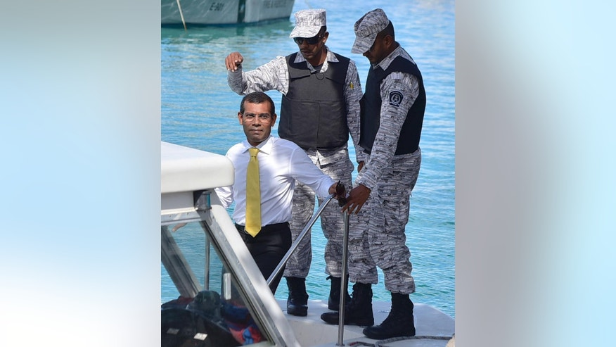 Maldives former president Mohamed Nasheed, left, prepares to leave on a speedboat, apparently headed to an island jail, after appearing at the High Court in Male, Maldives, Wednesday, Sept. 9, 2015. Nasheed is currently in prison after a Maldivian court in March found him guilty of ordering the military to detain a senior judge when he was president three years ago. (AP Photo/ Mohamed Sharuhaan)