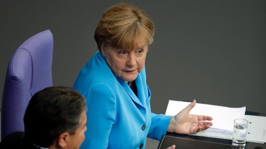 German Chancellor Angela Merkel, right, gestures as she talks to Vice Chancellor Sigmar Gabriel, left, after her speech as part of a meeting of the German Federal Parliament, Bundestag, at the Reichstag building in Berlin, Germany, Wednesday, Sept. 9, 2015. (AP Photo/Michael Sohn)