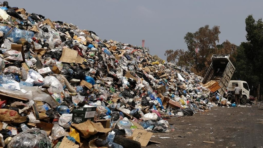 A dump truck adds trash to a pile of garbage on the bank of the Beirut River, in Beirut, Lebanon, Monday, Sept. 7, 2015. Lebanon has been witnessing a wave of anti-government rallies, sparked by the government's inability to solve an ongoing trash crisis. Those rallies have been led by civil society groups who came together to protest government corruption that led to the latest gridlock. (AP Photo/Hassan Ammar)