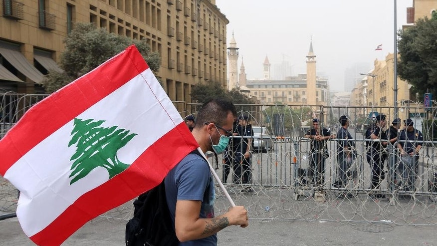 A Lebanese anti-government protester holds his national flag as Lebanese riot policemen stand guard behind barbed wire that blocks a road leading to the parliament building, during a protest against the on-going trash crisis and government corruption, in downtown Beirut, Lebanon, Wednesday, Sept. 9, 2015. Lebanon's prime minister says he hopes that political talks between senior politicians will help end government paralysis that has sparked angry street protests. (AP Photo/Bilal Hussein)