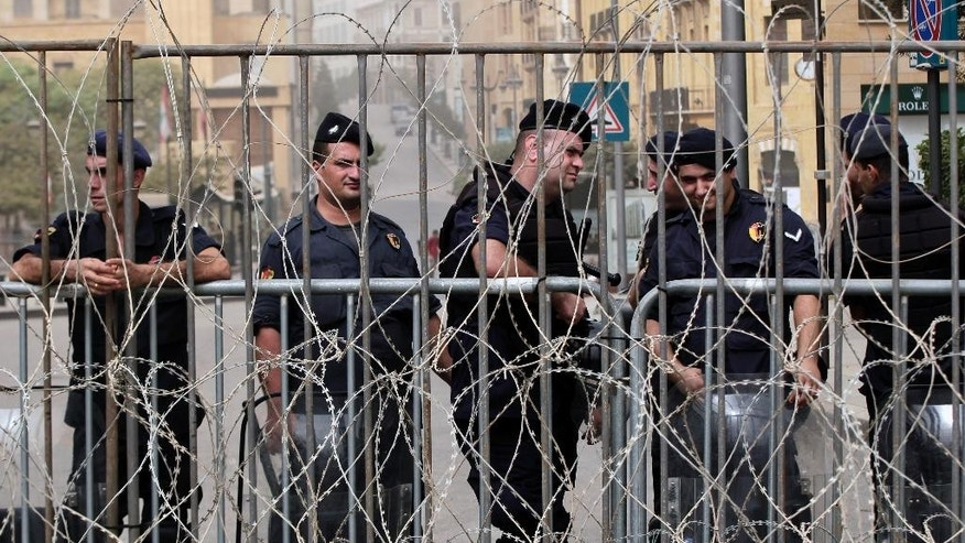 Lebanese riot policemen stand guard behind barbed wire that blocks a road leading to the parliament building, during a protest against the on-going trash crisis and government corruption, in downtown Beirut, Lebanon, Wednesday, Sept. 9, 2015. Lebanon's prime minister says he hopes that political talks between senior politicians will help end government paralysis that has sparked angry street protests. (AP Photo/Bilal Hussein)