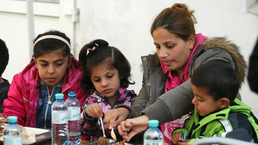 A woman and children sit and eat their food during Turkish born Aytekin Yilmazer's 37th birthday party at the refugee camp in Traiskirchen, Austria, Wednesday, Sept. 9, 2015. Yilmazer's bash will be a night to remember _ both for him and the hundreds of refugees from Syria, Afghanistan and other troubled corners of the world who took up his invitation Wednesday to celebrate his 37th birthday. (AP Photo/Ronald Zak)