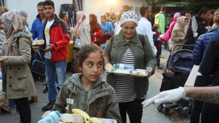A child carries a tray of food during Turkish born Aytekin Yilmazer's 37th birthday party at the refugee camp in Traiskirchen, Austria, Wednesday, Sept. 9, 2015. Yilmazer's bash will be a night to remember _ both for him and the hundreds of refugees from Syria, Afghanistan and other troubled corners of the world who took up his invitation Wednesday to celebrate his 37th birthday. (AP Photo/Ronald Zak)