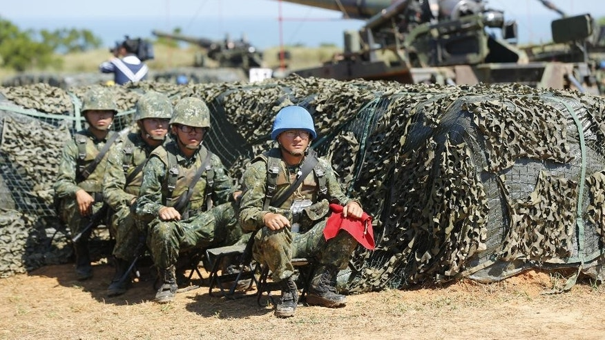 Taiwan's military rest behind self-propelled Howitzers during the annual Han Kuang exercises in Hsinchu, north eastern Taiwan, Thursday, Sept. 10, 2015. Taiwan's military is simulating attacks by political rival China this week, despite an overall warming of ties, after Beijing staged what appeared to be a strike against the presidential office in Taipei. (AP Photo/Wally Santana)
