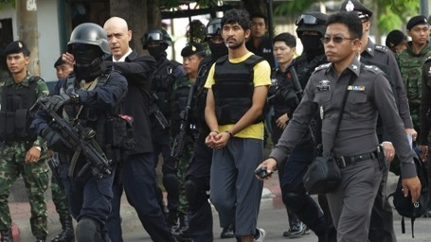 Sept. 9, 2015: Police officers escort a key suspect in last month's Bangkok bombing, center in yellow shirt, identified by Thai police as Yusufu Mierili, also as Yusufu Mieraili, outside Hua Lamphong railway station during a reenactment for the Aug. 17 bombing at the popular Erawan Shrine that left 20 people dead and more than 120 injured. (AP Photo/Sakchai Lalit)