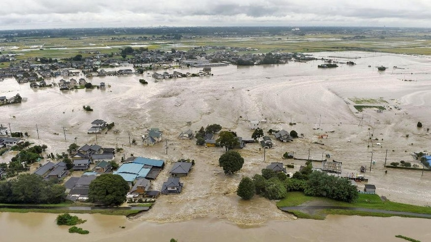 Houses are submerged in water flooded from a river in Joso, Ibaraki prefecture, northeast of Tokyo Thursday, Sept. 10, 2015. Heavy rain is pummeling Japan for a second straight day, overflowing rivers and causing landslides and localized flooding in the eastern part of the country. (Kyodo News via AP) JAPAN OUT, MANDATORY CREDIT