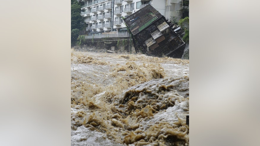 A building of an open-air spa, right, that belongs to Kinugawa Plaza Hotel, falls into the rapid stream of the Kinugawa River swollen by heavy rainfall in Nikko, Tochigi prefecture, northeast of Tokyo Thursday, Sept. 10, 2015. Heavy rain is pummeling Japan for a second straight day, overflowing rivers and causing landslides and localized flooding in the eastern part of the country. (Kyodo News via AP) JAPAN OUT, MANDATORY CREDIT