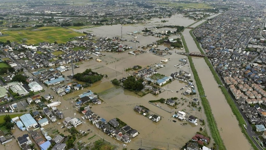 People inside houses wait to be rescued as the houses are submerged in water flooded from a river in Joso, Ibaraki prefecture, northeast of Tokyo Thursday, Sept. 10, 2015. Heavy rain is pummeling Japan for a second straight day, overflowing rivers and causing landslides and localized flooding in the eastern part of the country. (Kyodo News via AP) JAPAN OUT, MANDATORY CREDIT
