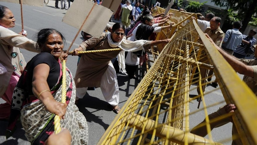 Activists of All India Democratic Women's Association try to bring down a police barricade during a protest outside the Saudi Arabian embassy in New Delhi, India, Thursday, Sept. 10, 2015. Police in India were investigating complaints from two women that a Saudi Arabian diplomat raped them repeatedly and confined them in his home near New Delhi. He has claimed diplomatic immunity, and the Saudi embassy in a statement Wednesday denied all the allegations. (AP Photo/Altaf Qadri)