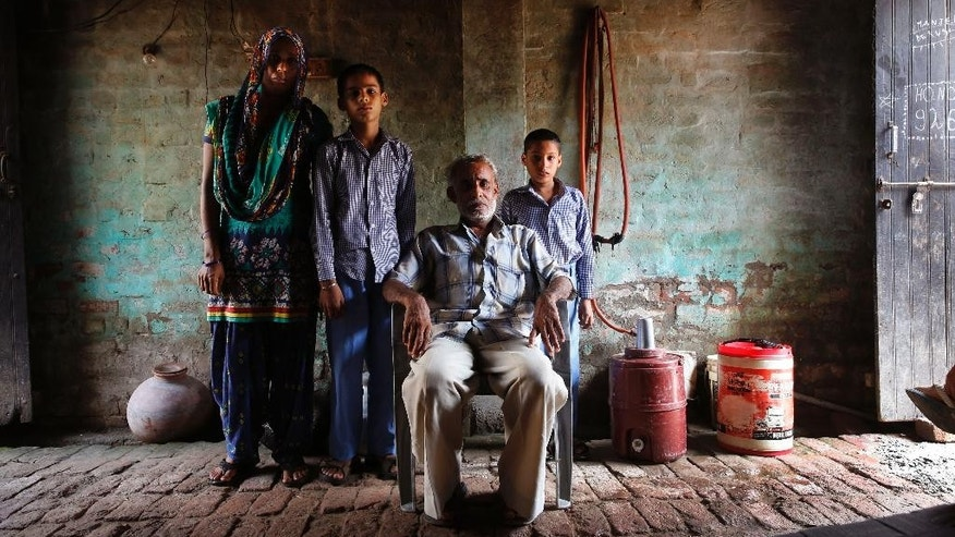 In this Aug. 13, 2015, photo, Anita Berwal, left,  from the Indian southern state of Kerala, married to Sadhuram Berwal, sitting, pose for a family photograph with their children in their house in Sorkhi village, 150 kilometers  (93 miles) west of New Delhi, in the Indian state of Haryana.  Sadhuram Berwal traveled  2,700 kilometers (1,700 miles) to meet Anita and bring her to his home state of Haryana, known for its shortage of brides -- the direct consequence of the skewed gender ratio in the state, due to sex-selective abortions in a society where many families prize boys over girls, mostly for economic reasons.  But women who move to Haryana to get married _ especially those from the better-off south _ face enormous adjustments, practical and cultural. (AP Photo/Manish Swarup)