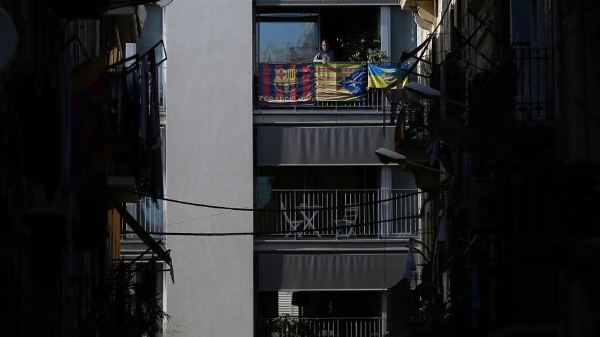 In this photo taken Wednesday, Sept. 9, 2015, a man looks on from a balcony decorated with an Estelada flag, centre, (pro-independence Catalan flag) in Barcelona. For a fourth consecutive year, hundreds of thousands of pro-independence Catalans are expected to rally Friday to break away from Spain, kicking off a fresh secession bid in a push to carve out a new European nation. (AP Photo/Manu Fernandez)