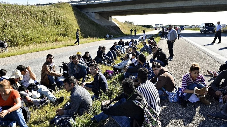 A group of refugees and migrants who were walking north sit down on the highway in southern Denmark on Wednesday, Sept. 9, 2015.  The migrants have crossed the border from Germany, and after staying at a local school, they say they are now making their way to Sweden, to seek asylum. (Ernst van Norde/Polfoto via AP) DENMARK OUT