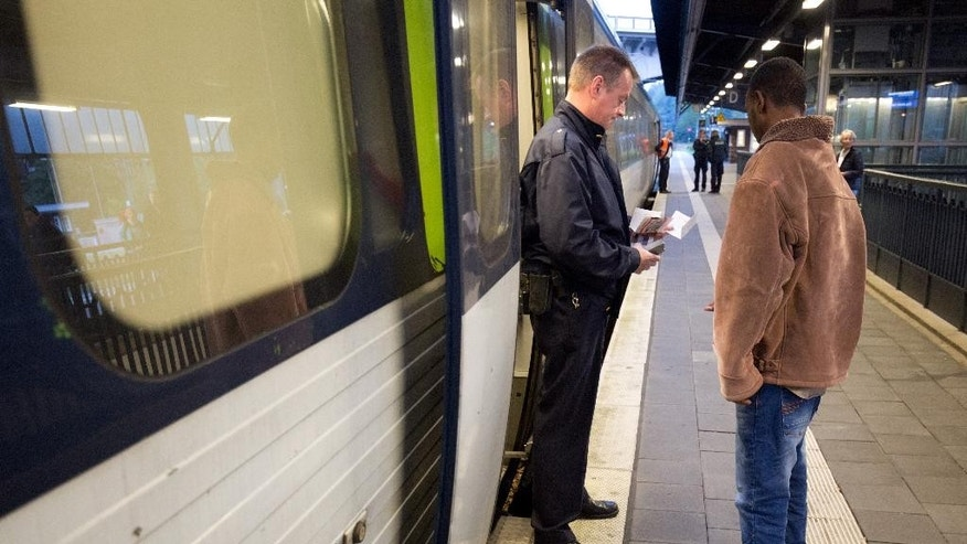 A Danish train conductor checks the ticket of 19-years-old Abdullah from Somalia who is on his way to his mother in Sweden in the train station in Flensburg, northern Germany, Thursday, Sept. 10, 2015. On Wednesday Danish railway company DSB said all train service had been halted between Germany and Denmark after Danish police stopped hundreds of migrants arriving by train across the border. (Christian Charisius/dpa via AP)