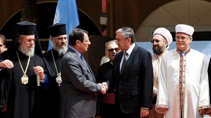 Cyprus' president Nicos Anastasiades, Turkish Cypriot leader Mustafa Akinci shake hands as the Greek Cypriot Orthodox Archbishop Chrysostomos II, left, and the Turkish Cypriot religious leader Mufti Yalip Atalay look on after a meeting at UN buffer zone at Ledra palace hotel in divided capital Nicosia, Cyprus, Thursday, Sept. 10, 2015. The heads of Cyprus' Christian and Muslim communities are meeting with the ethnically divided island's rival leaders to lend their support to ongoing reunification talks. (AP Photo/Petros Karadjias)