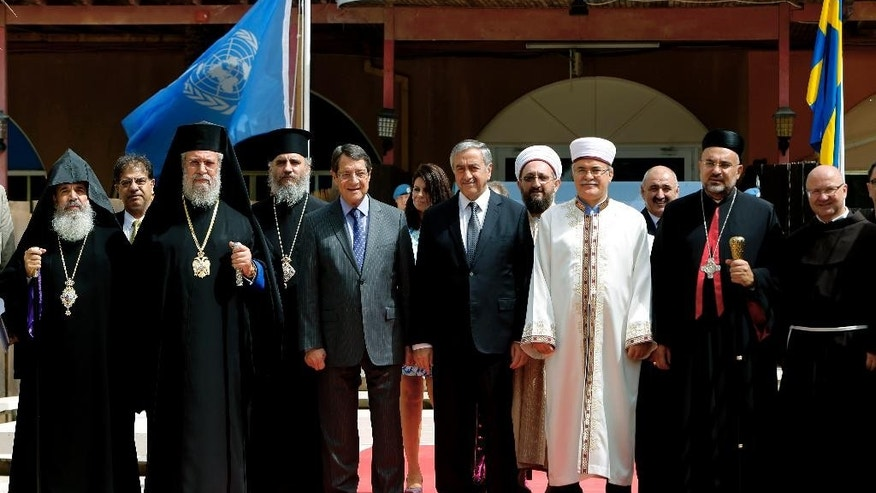 From left, front line, Armenian Orthodox church Nareg, Greek Cypriot Orthodox Archbishop Chrysostomos II, Cyprus' president Nicos Anastasiades, Turkish Cypriot leader Mustafa Akinci, Turkish Cypriot religious leader Mufti Yalip Atalay, Maronite church Archbishop Soueif and Latin catholic church Rev Jerzy Kraj pose for photo after a meeting at UN buffer zone at Ledra palace hotel in divided capital Nicosia, Cyprus, Thursday, Sept. 10, 2015. The heads of Cyprus' Christian and Muslim communities are meeting with the ethnically divided island's rival leaders to lend their support to ongoing reunification talks. (AP Photo/Petros Karadjias)