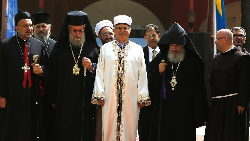 From left, the Maronite church Archbishop Soueif, Greek Cypriot Orthodox Archbishop Chrysostomos II, Turkish Cypriot religious leader Mufti Yalip Atalay, Armenian Orthodox church Nareg and Latin catholic church Rev Jerzy Kraj pose for photo before a meeting with Cyprus' president Nicos Anastasiades and Turkish Cypriot leader Mustafa Akinci, at UN buffer zone at Ledra palace hotel in divided capital Nicosia, Cyprus, Thursday, Sept. 10, 2015. The heads of Cyprus' Christian and Muslim communities are meeting with the ethnically divided island's rival leaders to lend their support to ongoing reunification talks. (AP Photo/Petros Karadjias)
