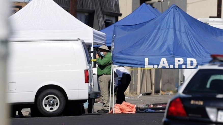 An LAPD investigator photographs a crime scene, where three children were been found dead inside a car.