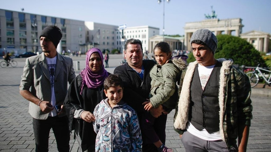 Laith Majid, a refugee from Iraq, center, holds his daughter Nour on his arm as he poses with his family, son Mustafa, left, his wife Neda, second from left, son Taha, front, and son Ahmed, right, for a photo in front of the Brandenburg Gate  in Berlin, Germany, Thursday, Sept. 10, 2015.  A photo of Laith Majid taken by a photographer Daniel Etter for the New York Times as he arrives at the Greece island Kos had goes viral on social media around the world. The other persons of  the family of Laith Majid Al-Amirij are, from left, son Ahmed, wife Neda,son Taha, son Mustafa (back) and daughter Nour. After fleeing from Iraq via Turkey and Greece they came to Germany were they live in an asylum seekers shelter in Berlin. (AP Photo/Markus Schreiber)
