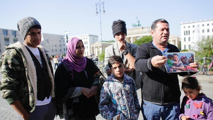 Laith Majid, second from right, a refugee from Iraq, stands in front of the Brandenburg Gate as he shows to media a photo from his arrival at the  Greek island of Kos, taken by photographer Daniel Etter for the New York Times in Berlin, Germany, Thursday, Sept. 10, 2015.  The other persons of  the family of Laith Majid, are, from left, son Ahmed, wife Neda,son Taha, son Mustafa (back) and daughter Nour. After fleeing from Iraq via Turkey and Greece they came to Germany were they live in an asylum seekers shelter in Berlin.   (AP Photo/Markus Schreiber) PICTURE MUST BE USED IN ITS ENTIRETY - NO CROPPING