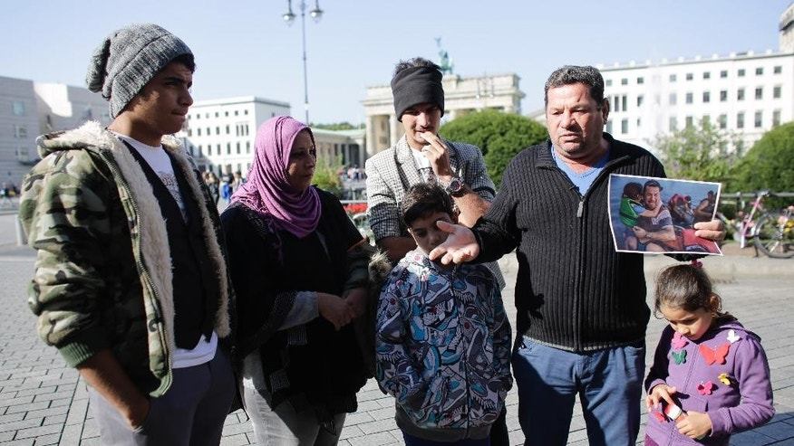 Laith Majid, second from right, a refugee from Iraq, stands in front of the Brandenburg Gate as he shows to media a photo from his arrival at the  Greek island of Kos, taken by photographer Daniel Etter for the New York Times in Berlin, Germany, Thursday, Sept. 10, 2015.  The other persons of  the family of Laith Majid Al-Amirij are, from left, son Ahmed, wife Neda,son Taha, son Mustafa (back) and daughter Nour. After fleeing from Iraq via Turkey and Greece they came to Germany were they live in an asylum seekers shelter in Berlin. (AP Photo/Markus Schreiber) PICTURE MUST BE USED IN ITS ENTIRETY - NO CROPPING