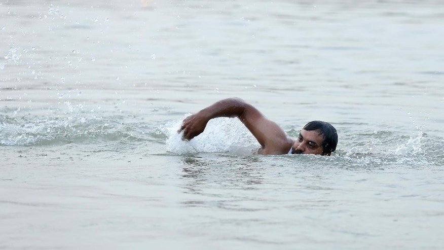 In this Wednesday, Sept. 9, 2015 photo, Mustafa Jassim Mohammed, 29, practices paddling with an arm maimed in a bombing as he swims in the Tigris River in preparation to face the danger of crossing the Mediterranean Sea, in the Azamiyah neighborhood in Baghdad, Iraq. He knows that migrants -- men, women and children -- have died when their smuggler boats capsized, and he's seen the heart-wrenching pictures of the drowned Syrian boy who washed ashore in Turkey last week. But he's also seen the TV footage of hundreds of migrants making their way across Europe and being welcomed in certain quarters. After more than a decade of chaos and war, it's a gamble he's willing to take.(AP Photo/Hadi Mizban)