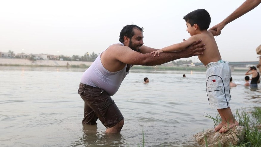 In this Wednesday, Sept. 9, 2015 photo, Mustafa Jassim Mohammed, 29, is joined by his son as he practices swimming in the Tigris River in the Azamiyah neighborhood in Baghdad, Iraq, in preparation for his Mediterrenean Sea voyage en route to Europe. His wife and two children will stay behind, praying for his safety and hoping to be reunited with him somewhere safer. Like many Iraqis, he's wanted to leave for years, but is only doing so now because he's seen footage of migrants being welcomed in Germany and Austria. (AP Photo/Hadi Mizban)