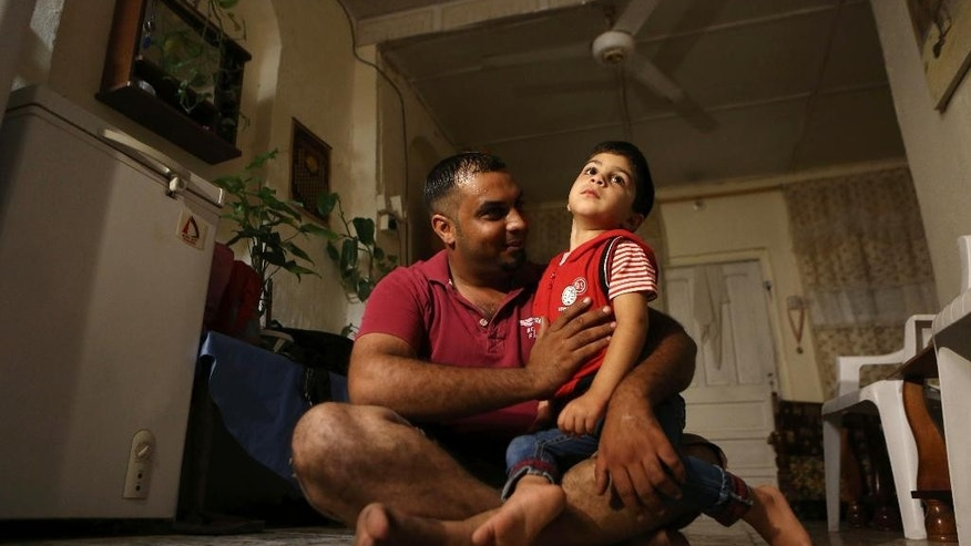 In this Wednesday, Sept. 9, 2015 photo, Mustafa Jassim Mohammed, 29, plays with his son shortly before his journey to Europe at Azamiyah neighborhood in Baghdad, Iraq. He quit his two jobs, as a civil servant and a tea seller, and sold his belongings to buy a one-way ticket to Iraq's northern Kurdish region, where he'll cross into Turkey and join an unprecedented tide of migrants fleeing war and poverty across the Middle East and South Asia. His wife and two children will stay behind, praying for his safety and hoping to be reunited with him somewhere safer.(AP Photo/Hadi Mizban)