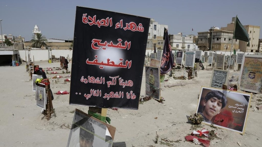 FILE- In this Saturday, May 30, 2015 file photo, religious flags, photographs and tributes to 21 victims of a suicide bombing, claimed by the Islamic State group, of a Shiite mosque are seen attached to their graves at a cemetery in Qudeeh, Saudi Arabia. The Islamic State group is extending its reach in Saudi Arabia, expanding the scope of its attacks and drawing in new recruits with its radical ideology. Its determination to bring down the U.S.-allied royal family has raised concerns it could threaten the annual Muslim hajj pilgrimage later this month. (AP Photo/Hasan Jamali, File)