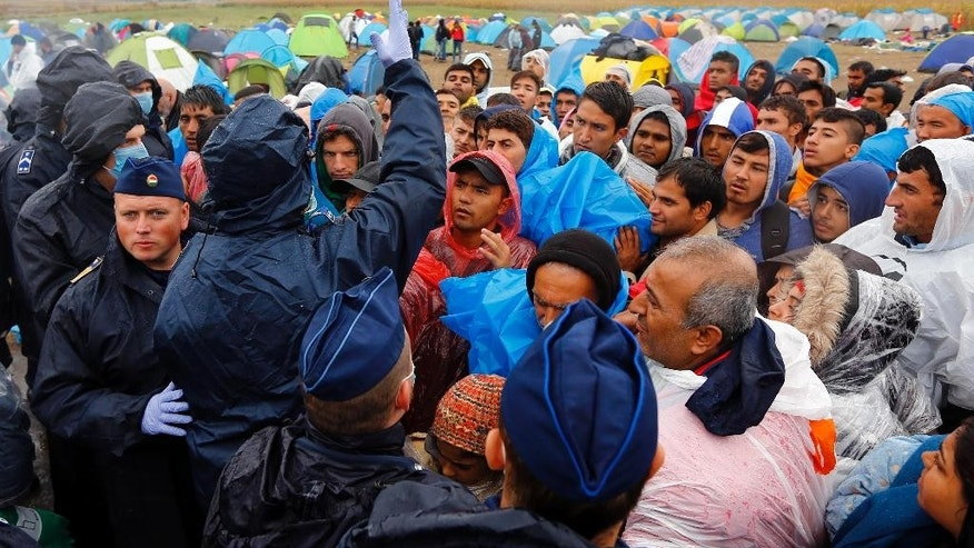 Migrants wait for a bus that will take them to the center for asylum seekers near Roszke, southern Hungary in Roszke, Thursday, Sept. 10, 2015. Leaders of the United Nations refugee agency warned Tuesday that Hungary faces a bigger wave of 42,000 asylum seekers in the next 10 days and will need international help to provide shelter on its border, where newcomers already are complaining bitterly about being left to sleep in frigid fields. (AP Photo/Matthias Schrader)