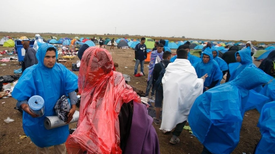 Migrants prepare for rain at a makeshift camp for asylum seekers in Roszke, southern Hungary, Thursday, Sept. 10, 2015. Leaders of the United Nations refugee agency warned Tuesday that Hungary faces a bigger wave of 42,000 asylum seekers in the next 10 days and will need international help to provide shelter on its border, where newcomers already are complaining bitterly about being left to sleep in frigid fields. (AP Photo/Darko Vojinovic)