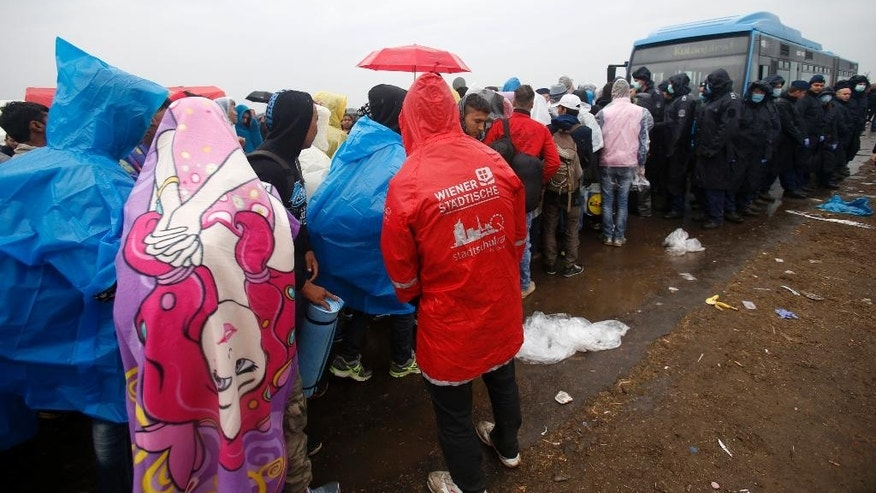 Migrants wait in the rain for a bus that will take them to the center for asylum seekers near Roszke, southern Hungary, Thursday, Sept. 10, 2015. Leaders of the United Nations refugee agency warned Tuesday that Hungary faces a bigger wave of 42,000 asylum seekers in the next 10 days and will need international help to provide shelter on its border, where newcomers already are complaining bitterly about being left to sleep in frigid fields. (AP Photo/Darko Vojinovic)