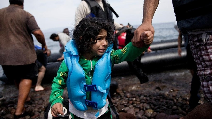 A young migrant girl is helped ashore as she arrives with others aboard a dinghy after crossing from Turkey to Lesbos island, Greece, Wednesday, Sept. 9, 2015. The head of the European Commission, Jean-Claude Juncker issued an impassioned plea Wednesday for Europe to face up to its immigration crisis.(AP Photo/Petros Giannakouris)