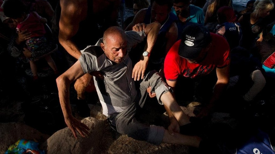 An elderly refugee is being helped to get out of a dinghy after he crossed with others from Turkey to Lesbos island, Greece, Tuesday, Sept. 8, 2015.  The island of some 100,000 residents has been transformed by the sudden new population of some 20,000 migrants, mostly from Syria, Iraq and Afghanistan. (AP Photo/Petros Giannakouris)