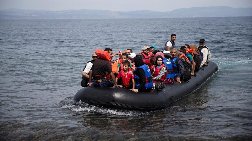 Migrants arrive on a dinghy after crossing from Turkey to Lesbos island, Greece, Wednesday, Sept. 9, 2015. The head of the European Commission, Jean-Claude Juncker issued an impassioned plea Wednesday for Europe to face up to its immigration crisis. (AP Photo/Petrmigrantos Giannakouris)