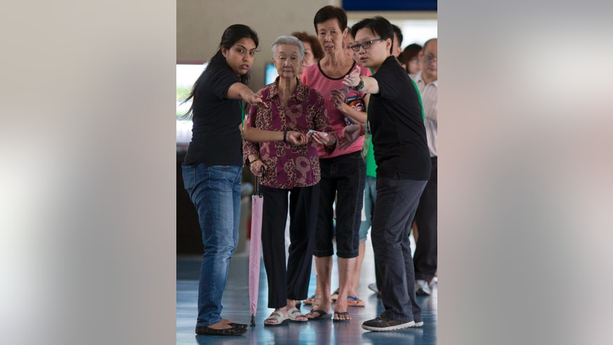 Singaporeans prepare to vote at a polling station in Singapore, Friday, Sept. 11, 2015. Singaporeans began voting Friday in general elections whose results hold no surprises - the ruling People's Action Party will extend its 50-year-rule by another five years. (AP Photo/Ng Han Guan)