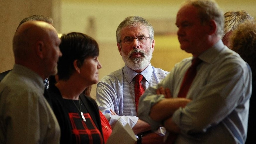 Sinn Fein party leader Gerry Adams, centre, with party members Alex Maskey, left, and Martin McGuinness, front right, wait to speak to the media at Parliament Buildings, Stormont, Belfast, Northern Ireland, Thursday, Sept. 10, 2015.  A political crisis at Stormont has developed over the recent murder of Kevin McGuigan and the status of the IRA, and the viability of the Catholic-Protestant power-sharing government. (AP Photo/Peter Morrison)