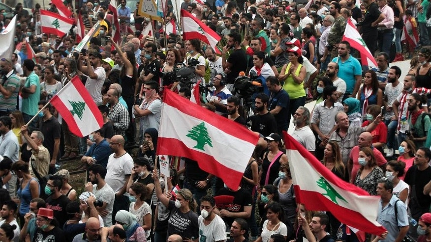 Lebanese anti-government protesters shout slogans as they hold their national flags, during a protest against the on-going trash crisis and government corruption, in downtown Beirut, Lebanon, Wednesday, Sept. 9, 2015. Lebanon's prime minister says he hopes that political talks between senior politicians will help end government paralysis that has sparked angry street protests. (AP Photo/Bilal Hussein)