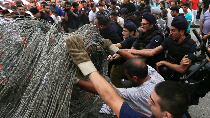 Lebanese riot policemen remove barbed wire that blocks a road leading to the parliament building after meetings among political leaders as people protest against the on-going trash crisis and government corruption in downtown Beirut, Lebanon, Wednesday, Sept. 9, 2015. Lebanon's Prime Minister Tammam Salam said he hopes that political talks among senior politicians will help end government paralysis that has sparked angry street protests. (AP Photo/Hassan Ammar)