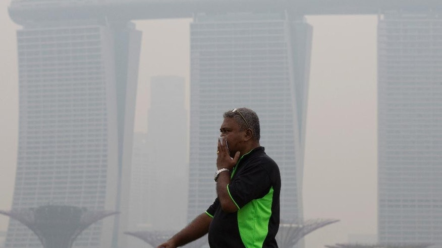 A man covers his nose during a hazy day in Singapore, Thursday, Sept. 10, 2015. Air pollution in Singapore reached its highest level in a year on Thursday as smog from Indonesian forest fires shrouded the island nation in a veil of gray, irking tourists and alarming authorities with hours left before general elections. (AP Photo/Ng Han Guan)