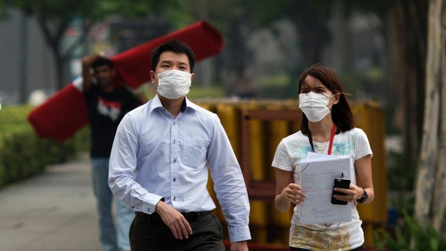 A man and woman wear masks as they work outdoor during a hazy day in Singapore, Thursday, Sept. 10, 2015. Air pollution in Singapore reached its highest level in a year on Thursday as smog from Indonesian forest fires shrouded the island nation in a veil of gray, irking tourists and alarming authorities with hours left before general elections. (AP Photo/Ng Han Guan)