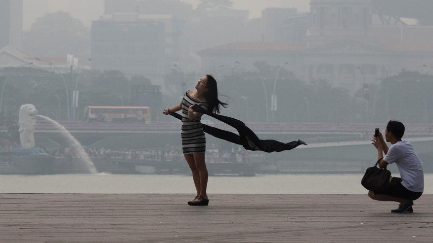 A woman poses for photos during a hazy day in Singapore, Thursday, Sept. 10, 2015. Air pollution in Singapore reached its highest level in a year on Thursday as smog from Indonesian forest fires shrouded the island nation in a veil of gray, irking tourists and alarming authorities with hours left before general elections. (AP Photo/Ng Han Guan)