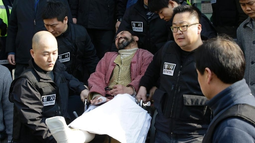 In this March 6, 2015 photo, South Korean Kim Ki-jong in a wheelchair is carried by police officers as he leaves a police station for Seoul Central District Court in Seoul, South Korea. The court on Friday, Sept. 11, 2015, handed a 12-year prison sentence to Kim who slashed and seriously injured the U.S. Ambassador Mark Lippert during a March forum. Kim was convicted of attempted murder, assaulting a foreign envoy and obstruction, according to court spokesman Joon Young Maeng.Kim Ki-jong, center, the suspect of slashing U.S. Ambassador Mark Lippert, in a wheelchair is carried by police officers as he leaves a police station for Seoul Central District Court in Seoul, South Korea. A Seoul court on Friday handed a 12-year prison sentence to a South Korean man who slashed and seriously injured the U.S. ambassador during a March forum. (AP Photo/Lee Jin-man)