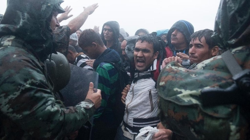 A migrant shouts as he waits to pass  from the northern Greek village of Idomeni to southern Macedonia, Thursday, Sept. 10, 2015. Thousands of people, including many families with young children, braved torrential downpours to cross Greece's northern border with Macedonia early Thursday, after Greek authorities managed to register about 17,000 people on the island of Lesbos in the space of a few days, allowing them to continue their journey north into Europe. (AP Photo/Giannis Papanikos)