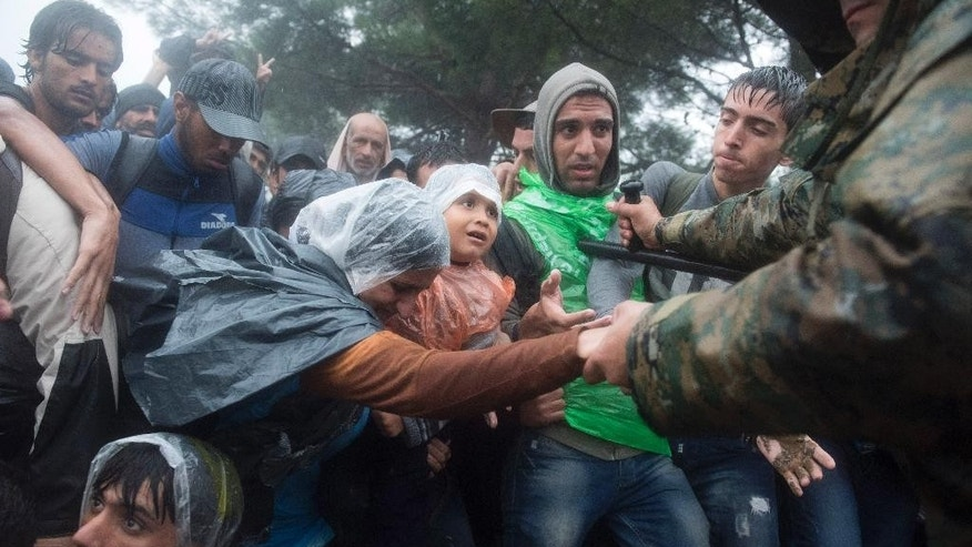 Macedonian border police helps refugees and migrants to pass in  heavy rainfall from the northern Greek village of Idomeni to southern Macedonia, Thursday, Sept. 10, 2015. Thousands of people, including many families with young children, braved torrential downpours to cross Greece's northern border with Macedonia early Thursday, after Greek authorities managed to register about 17,000 people on the island of Lesbos in the space of a few days, allowing them to continue their journey north into Europe. (AP Photo/Giannis Papanikos)