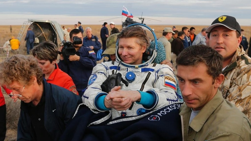 Rescue workers carry Russian cosmonaut Gennady Padalka after the Russian Soyuz TMA-16M capsule carrying a crew of Padalka, Andreas Mogensen of the European Space Agency and Kazakhstan's Aidyn Aimbetov landing some 146 kilometers (90 miles) southeast of town of Dzhezkazgan, Kazakhstan, early Saturday, Sept. 12, 2015. (Yuri Kochetkov/Pool Photo via AP)
